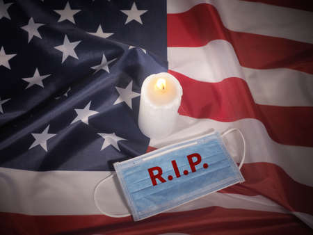Candle-light ceremony and face mask on USA flag background. Covid-19 victims. 版權商用圖片