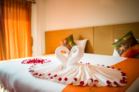 romance bed: love swans and rose decoration in hotel
