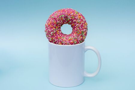 Delicious, appetizing, beautiful, pink doughnut in a mug with a drink. Breakfast, snack, lunch. The white mug without logos is perfect for the loyal advertising as a layout. Photo in pastel tones.
