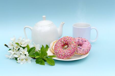 photo in pastel colors. A white teapot and a mug with a hot drink and three delicious donuts and a sprig of blossoming apple tree, which creates a romantic mood. Without logos, can be used as a layout Stock fotó