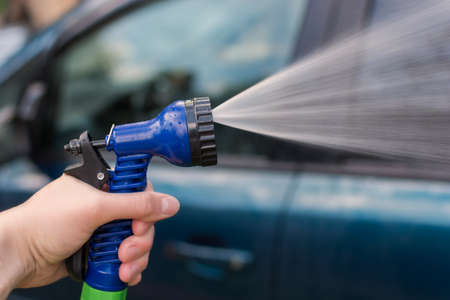 A womans hand holds a hose for washing the car. Water, spray, jet. The idea is to wash your car in front of your house, saving after a pandemic. Photo close-up, horizontal. Standard-Bild