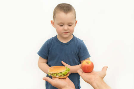 The little boy is given a choice of hamburger or apple.