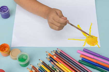 Close-up - a child's hand drawing the sun with paints on a white sheet of paper, next to it are colored pencils and markers. The idea is children's creativity. horizontal photo