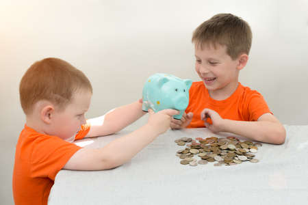 Two children in orange T-shirts on a light background shake coins from a piggy bank. One holds, the other laughs. The idea is that children have saved up for their cherished desire