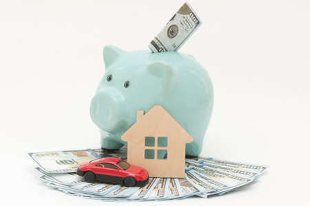 on a white background there is a piggy bank on a fan of 100-dollar bills, and a mock-up of a red car and a house. Concept - earnings, savings, financing, buying luxury goods, cars and real estate Stockfoto