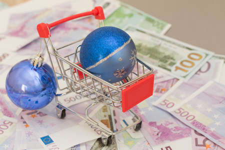 there is a blue christmas ball in the supermarket trolley. The cart is on euro and dollar bills. Concept - buying in an online store, delivering any product home, expenses, spending.