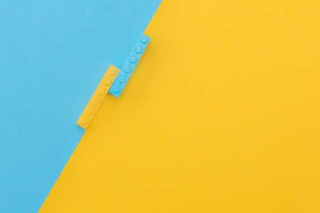 two small rectangular constructors in yellow and blue, lie on a yellow and blue background. Color contrast. Concept - Background, layout for advertising, place for text Banco de Imagens