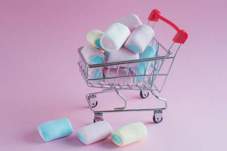 on a pink background a toy cart from a supermarket. It has a blue and pink marshmallow and three more lie side by side. Idea - buying sweets, selling goods, home delivery, preparing for the holiday. Imagens