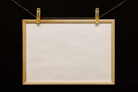 A wooden frame hangs on a rope with clips, clothes. Frame on a black background with a white space for dough, advertising or photo. horizontal photo. 免版税图像