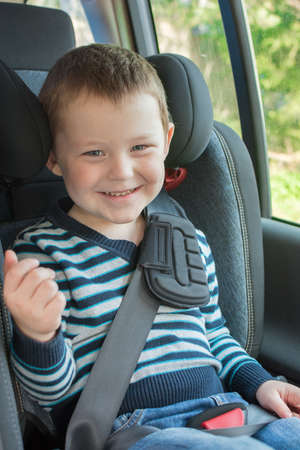 ittle boy sitting in car seat, smiling, looking at camera. The idea is the safety and convenience of children when driving, compliance with the rules for transporting children.