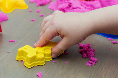 close-up of a childs hand playing with pink kinetic sand with a train mold. The idea is to develop fine motor skills, speech and creativity of the child.