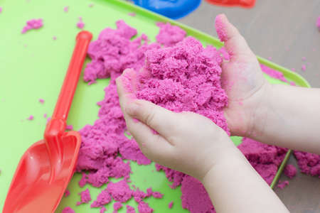 close-up of childrens palms with kinetic sand of bright pink color. The idea is the development of fine motor skills and creativity of the child.