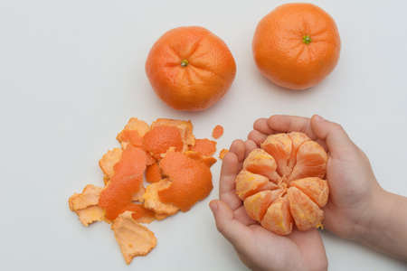 close-up, top view, on a white background, in children's palms there is a peeled tangerine, next to two more whole and skins. Concept - healthy food for children, lifestyle,