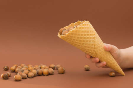 a waffle cone with a hazelnut in the childs hand, the cone is tilted and several nuts are poured out of it. Close-up, horizontal photo, brown background.