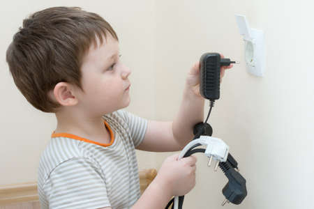 the child plays with electric plugs, holds several plugs in his hands and tries to insert into the socket. The idea is that children everywhere even at home are in danger, children need to be monitored.