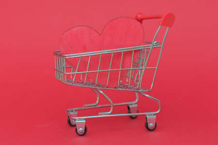 close-up of a small cart from a supermarket with a red heart on a red background. Horizontal photo. Фото со стока