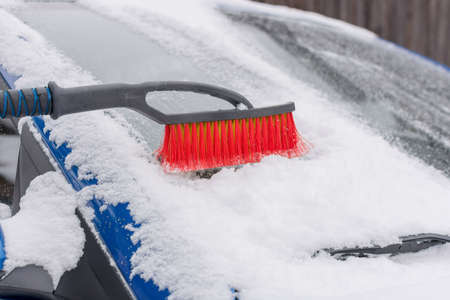 Brush for cleaning snow from a car close-up. A red-bristled brush rests on a snow-covered blue car. The idea is to clear the car of snow, winter problems, blizzards, cold. Horizontal photo.