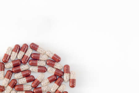 pills are scattered on a white background, brown with white granules inside. View from above. Horizontal photo. Place for your text