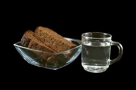 Bread and water in a glassware on a black background photo