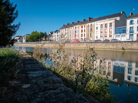 Buildings are reflected on the Sarthe River in the city of Le Mans in western France. Le Mans is an important city in the Pays de la Loire region. Filmed during the summer, sky with some clouds.