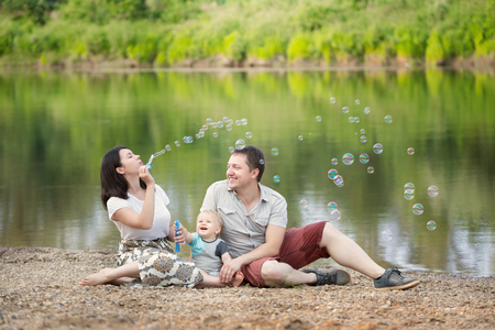 babyboy: Happy Family time concept. Young mother, father and his one year old blue-eyed son blowing bubbles in nature on the river bank