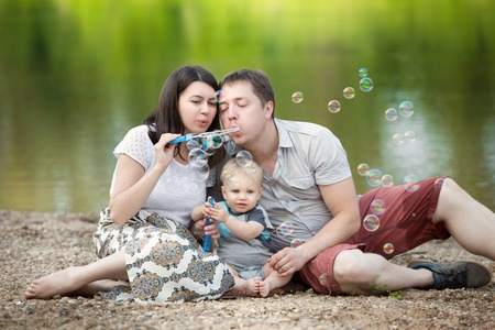 Happy Family time concept. Young mother, father and his one year old blue-eyed son blowing bubbles in nature on the river bank
