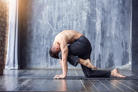 Young yogi men practices yoga asana, poses in urban studio. Yoga men workout on black mat.