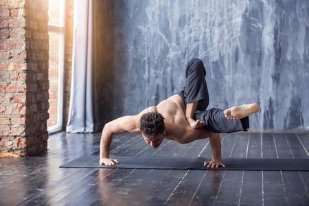 Jonge man doet een asana ashtavakrasana. Hand staande houding. Yogi hoofdtraining op zwarte mat op stedelijke studio. Kerel die yoga doen dichtbij een venster, levensstijl gezond concept Stockfoto