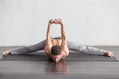 A young strong man doing yoga exercises. Studio shot over white brick background and black floor.