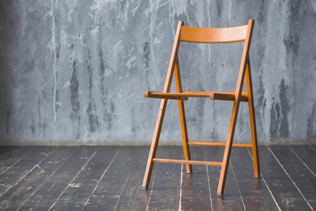 Brown wooden chair standing in front of a grey urban wall with mouldings on wooden black floor. Stock Photo