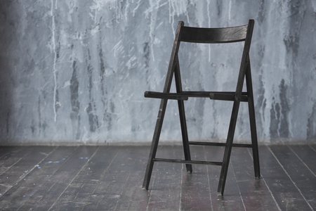 Black wooden chair standing in front of a grey urban wall with mouldings on wooden black floor.