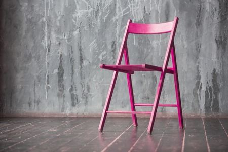 Pink wooden chair standing in front of a grey urban wall with mouldings on wooden black floor.