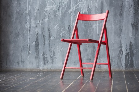 Red wooden chair standing in front of a grey urban wall with mouldings on wooden black floor.
