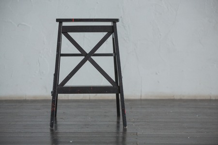 Black bar wooden chair standing in front of a grey urban wall with mouldings on wooden black floor.