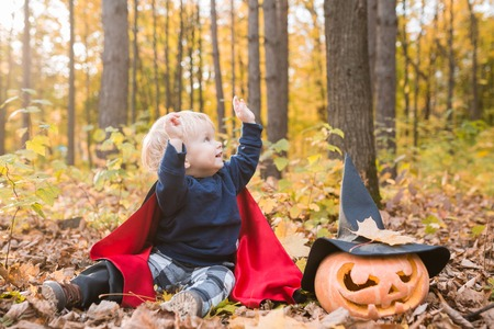 Portrait of Halloween smiling baby boy in dracula costume (cloak). Child in autumn forest looking at the falling leaves. Halloween pumpkin, witch hat, holiday concept