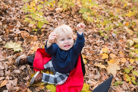 Halloween funny baby boy plays in dracula costume (cloak). 1 year-old Child in autumn forest looking at the falling leaves. Halloween pumpkin, witch hat, holiday concept