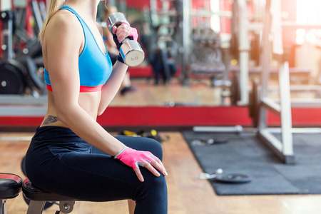 Close-up of a young woman exercising with weights in the gym. Fit girl with dumbbell. Sport and fitness concept