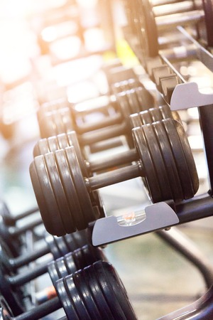 Fit barbell and dumbbells in the gym. Close up of many dumbell in sport fitness centre, equipment diversity