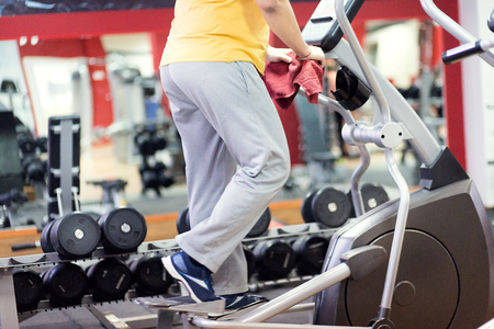 overweight man training on elliptic trainer in fitness centre, close up Stock Photo