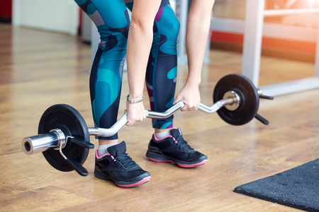 Young adult girl doing bench barbell in gym. Woman with muscular body doing lifting exercise. Fit women do fitness, workout sport concept, close up