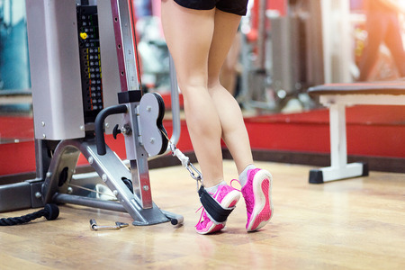 Close up of Athletic woman legs workout squats weighted lunges exercise for butt legs with suspension straps in fitness club or gym Stock Photo