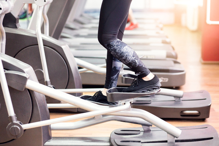 Young fit woman using an elliptic trainer in a fitness center, listening a music with headphones and smiling. Close up of legs of fitness girl in the gym. Stock Photo