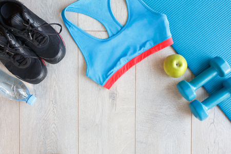 View from above of Fitness and sport equipment. Healthy lifestyle concept. Sneakers, sportswear, dumbbells, water, green apple on blue mat wooden floor background, top view