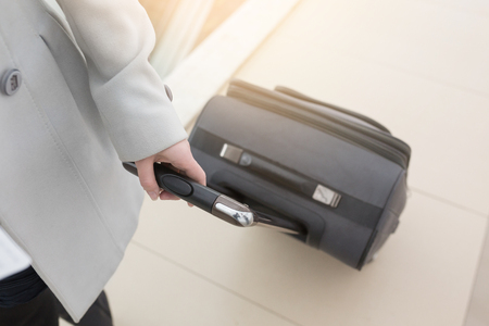 Business woman going with luggage or bag on her business trip. Close-up of women hands holding suitcase in modern airport terminal