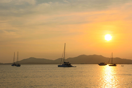 Sunset and dawn at sea against a backdrop of mountains and boats