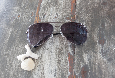 Sunglasses with shell and coral on a wooden table