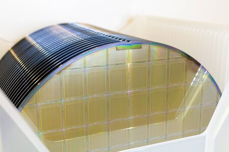 Silicon Wafers in white plastic holder box on table ,background is white color- A wafer is a thin slice of semiconductor material, such as a crystalline silicon, used in electronics for the fabrication of integrated circuits.Wafers with microchips.Rainbow on silicon wafers.Color silicon wafers with glare.