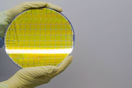 Silicon Wafer with microchips in the hands by gloves - A wafer is a thin slice of semiconductor material the fabrication of integrated circuits.Wafer with microchips.Rainbow on silicon wafers.Color silicon wafers with glare.