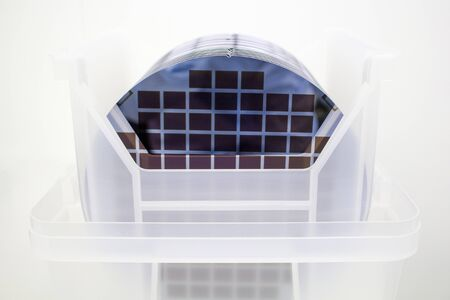 Silicon Wafers in white plastic holder box on table ,background is white color- A wafer is a thin slice of semiconductor material, such as a crystalline silicon, used in electronics for the fabrication of integrated circuits.