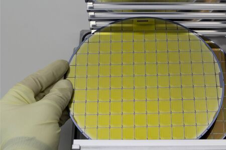 Silicon Wafers in steel holder box on table taken out by hand in gloves- A wafer is a thin slice of semiconductor material, such as a crystalline silicon.Wafer with microchips.Rainbow on silicon wafers.Color silicon wafers with glare. Stock Photo